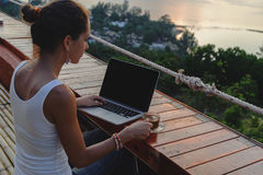 Woman sitting with a laptop and a cup of coffee in front of sunset view Royalty Free Stock Image