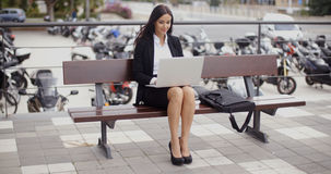 Woman sitting with laptop in front of motorcycles. Cute business woman sitting alone on bench in front of parked motorcycles while working on laptop computer Royalty Free Stock Photo