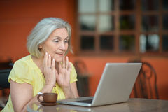 Woman sitting with laptop Stock Image