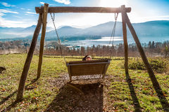 Woman sitting on a large swing with view Stock Photo