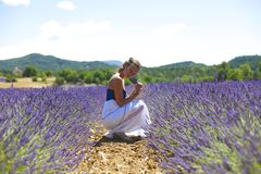Woman sitting on a lavender field Royalty Free Stock Photography