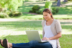 Woman sitting on the lawn with her laptop Royalty Free Stock Image