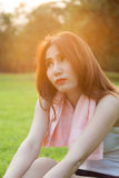Woman sitting on lawn in park. Stock Photography