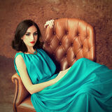 Woman sitting at leather armchair Royalty Free Stock Photos