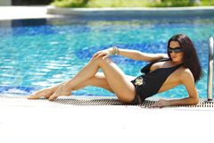 Woman sitting on the ledge of the pool stock photos