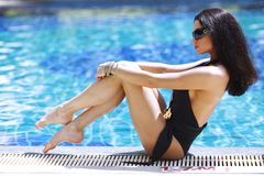 Woman sitting on the ledge of the pool Royalty Free Stock Photo