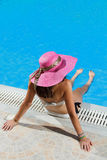 Woman sitting on the ledge of the pool. Royalty Free Stock Photos