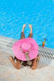 Woman sitting on the ledge of the pool. Stock Photos