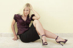 Woman sitting with legs crossed Stock Photography