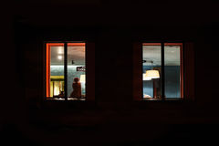 Woman sitting in a lighted room near window at night stock images