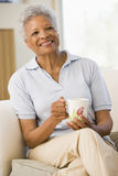 Woman sitting in living room with coffee smiling Stock Photography