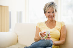 Woman sitting in living room with coffee smiling Stock Photos