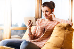 Woman sitting in the living room and listen to music Royalty Free Stock Image