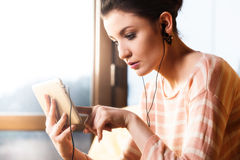 Woman sitting in the living room and listen to music Stock Image