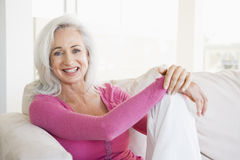 Woman sitting in living room smiling Stock Image