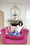 Woman sitting in living room smiling Royalty Free Stock Photos