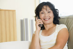 Woman sitting in living room using telephone Stock Photos