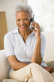 Woman sitting in living room using telephone Royalty Free Stock Images