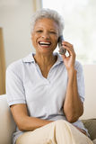 Woman sitting in living room using telephone Stock Images