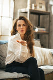 Woman sitting in loft apartment blowing kiss Royalty Free Stock Photos
