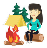 Woman sitting on log near campfire in the camping. Stock Photos