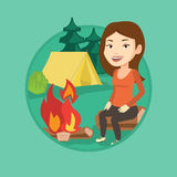 Woman sitting on log near campfire in the camping. Stock Image