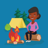 Woman sitting on log near campfire in the camping. Royalty Free Stock Photos