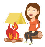 Woman sitting on log near campfire in the camping. Stock Photo