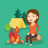 Woman sitting on log near campfire in the camping. Royalty Free Stock Images