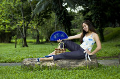Woman sitting on log with open fan royalty free stock image
