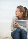 Woman sitting on lonely beach and embracing laptop Royalty Free Stock Image