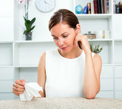 Woman sitting lonely indoors Stock Photo