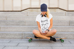 Woman sitting on longboard and texting. Girl sitting on longboard and texting Stock Image