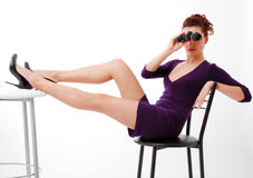 Woman sitting and looking on binoculars. Royalty Free Stock Photos