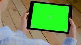 Woman looking at tablet computer with blank green screen - chroma key concept. Woman sitting and looking at black digital tablet computer device with blank green stock video