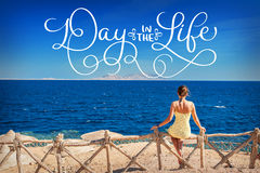 Woman sitting looking at the sea and text Day in the life. Calligraphy lettering vintage hand draw Stock Image
