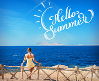 Woman sitting looking at the sea and text Hello Summer. Calligraphy lettering