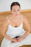 Woman sitting in lotus pose with eyes closed Stock Photography