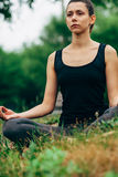 Woman sitting in lotus pose outdoors Royalty Free Stock Photography