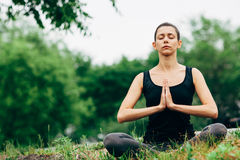 Woman sitting in lotus pose outdoors Royalty Free Stock Images
