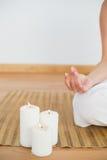 Woman sitting in lotus pose beside white candles royalty free stock photos