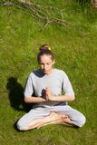 Woman sitting in a lotus position on green lawn. Young woman sitting in a lotus position on a green lawn Stock Photography