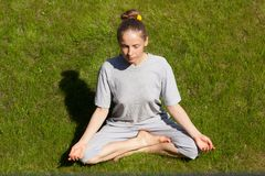 Woman sitting in a lotus position on green lawn. Young woman sitting in a lotus position on a green lawn Royalty Free Stock Photos