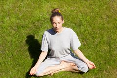 Woman sitting in a lotus position on green lawn. Young woman sitting in a lotus position on a green lawn Royalty Free Stock Photography