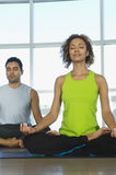 Woman Sitting In Lotus Position With Man In The Background Royalty Free Stock Photo