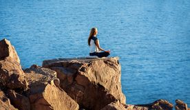 Woman Sitting in Lotus Position on Rock Above the Sea and Meditating. Yoga Outdoor Stock Photography
