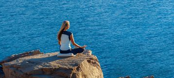 Woman Sitting in Lotus Position on Rock Above the Sea and Meditating. Yoga Outdoor. copyspase Stock Image