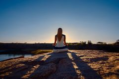 Woman Sitting in Lotus Position on Rock Above the Sea and Meditating. Yoga Outdoor. Sunset. Royalty Free Stock Photo