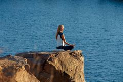 Woman Sitting in Lotus Position on Rock Above the Sea and Meditating. Yoga Outdoor Royalty Free Stock Photos