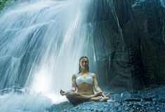 Woman sitting lotus yoga pose in spiritual relaxation serenity and meditation at stunning beautiful waterfall and rain forest in B. Attractive woman sitting Stock Image